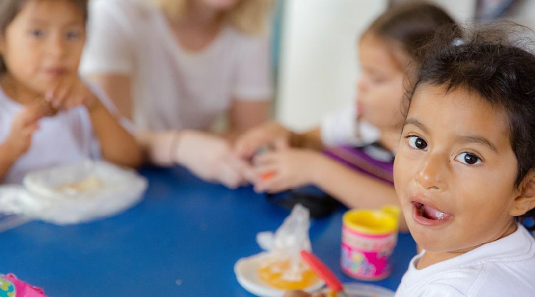 エクアドルで子供たちのランチタイムを補助する高校生ボランティア